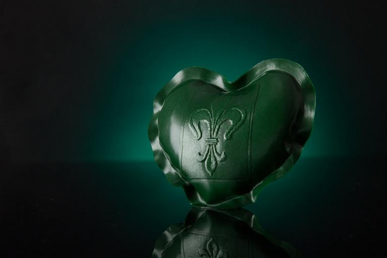 Grünes Herz aus Latex mit einer heraldischen Lilie